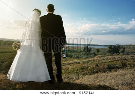 newlyweds with champaign at dawn