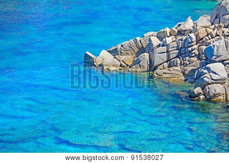 Grey Rocks On The Blue Water In Capo Testa