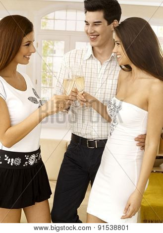 Young woman felicitating young couple on engagement, clinking glasses, celebrating with champagne.
