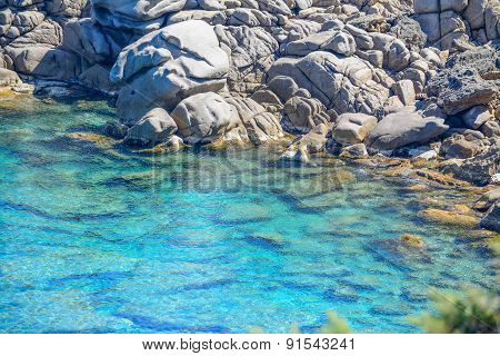 Grey Rocks And Green Plants By Capo Testa Clear Water