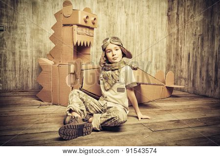 Cute dreamer boy playing with a cardboard airplane and dinosaur. Childhood. Fantasy, imagination. Retro style.