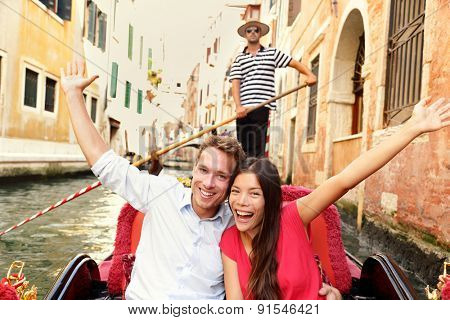 Tourists on travel happy couple in Venice gondola cheering excited joyful on travel. Romantic young beautiful couple on vacation holidays sailing in venetian canal in gondole. Italy. Asian woman.