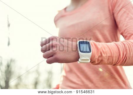 Heart rate monitor smart watch for sport. Athlete wearing heart rate monitor. Runner using sports smartwatch on running workout outside. Female athlete tracking activities using wearable technology. poster