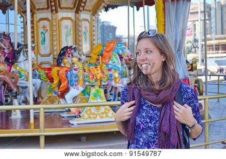 Young Girl Standing  In Front Of A Carousel