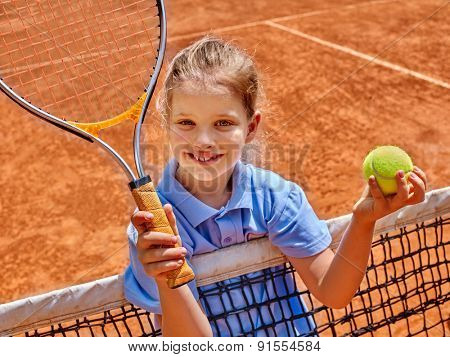 Kid athlete in blue form with racket and ball on  brown tennis court.