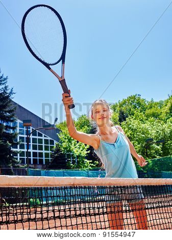 Girl teen sportsman with racket and ball near net on  tennis court.