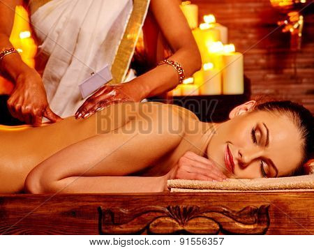Young woman having oil Ayurveda spa treatment. Burning candls.