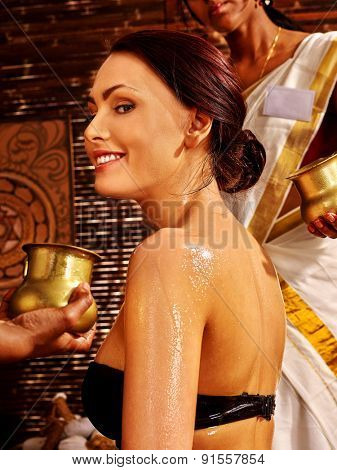 White young woman having oil Ayurveda spa treatment.