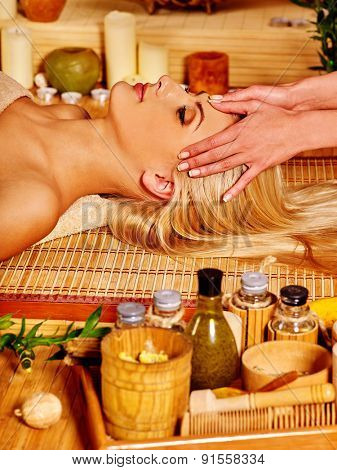 Woman with eyes clased getting facial massage in tropical beauty spa.