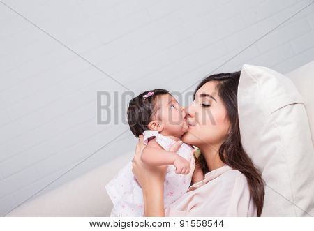 Happy mother kissing baby, cheerful joyful mom lying down with her adorable daughter on the couch at home, loving young family