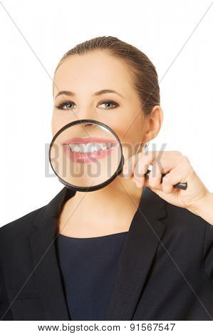 Close up on business woman's teeth through magnyfying glass.