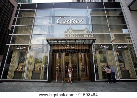 NEW YORK CITY - FRIDAY, MAY 8, 2015: Pedestrians walk past a Cartier jewelry store in New York City. Societe Cartier designs and sells jewellery and watches. Founded in Paris, France