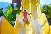 excited man having fun on water slide in tropical aqua park poster