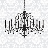 Vintage chandelier with candles and damask pattern behind poster