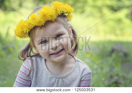 Happy and cheerful girl with a beautiful smile, with a wreath of dandelions.