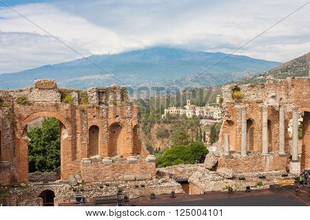 The ancient -roman-greek amphitheater with the Etna Volcano in the back in Taormina city Sicily Italy