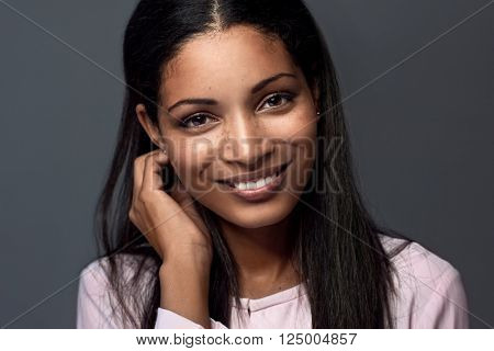 smiling portrait of a beautiful hispanic latino indian asian woman against dark grey background