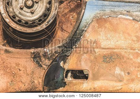 Close up detail of abandoned rusty burnt car wreck.