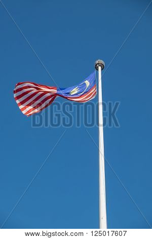 Malaysian national flag flying in wind on a pole with blue sky near Merdeka Square in Kuala Lumpur Malaysia.