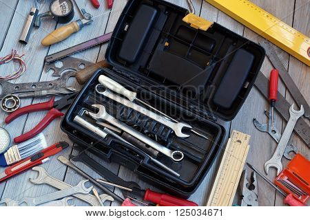 Open the tool box and tool around on the wooden floor top view. Locksmith and carpentry tools.
