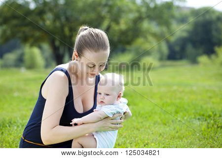 Beautiful young mother is holding her newborn son in the summer park