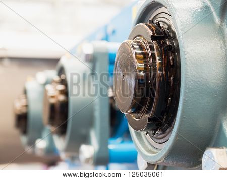 Ends of lubricated drive shafts exiting through ball bearings. Shallow depth of field with the nearest drive shaft in focus. poster