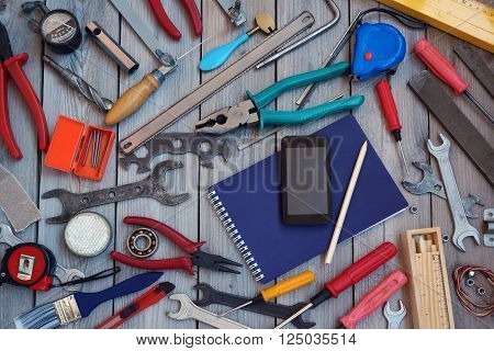 Notepad mobile phone and tool scattered around him on the wooden floor top view. Locksmith and carpentry tools.