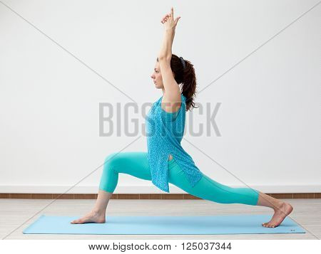 Yoga. Young Brunette Woman  In Warrior Pose