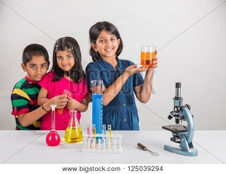 3 indian kids doing science experiment, science Education. asian kids and science experiments, chemistry experiment, indian kids and science experiments, indian kids and science lab