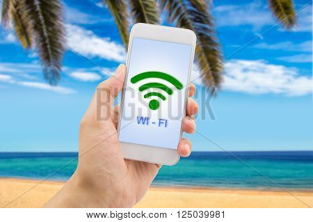 Hand holding mobile smart phone with connect wifi on the beach.
