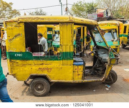 DELHI INDIA - 19TH MARCH 2016: Old Tuk Tuk Rickshaws parked on a street in central Delhi during the day. People can be seen.