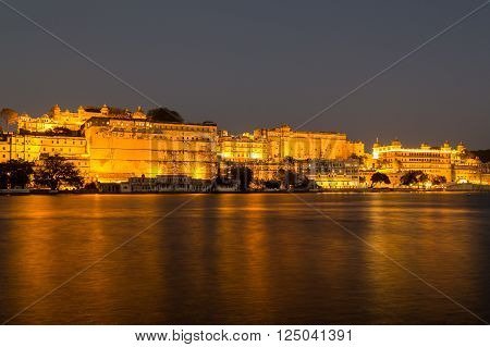 UDAIPUR INDIA - 20TH MARCH 2016: A view towards the City Palace from Pichola Lake in Udaipur at night. Lights can be seen on the building.