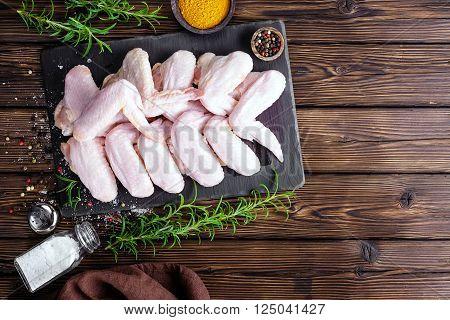 raw chicken wings on a bord on table