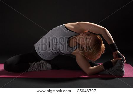 Young woman practicing yoga, Janu Sirsasana / Revolved Head-to-Knee Pose