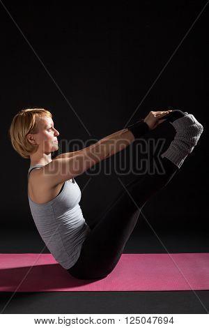 Young woman practicing yoga, Ubhaya Padangusthasana / Both Big Toes Pose poster