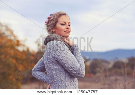 Beautiful smiling girl 20-24 year old wearing knitted sweater outdoors. Eyes closed. Young adults.