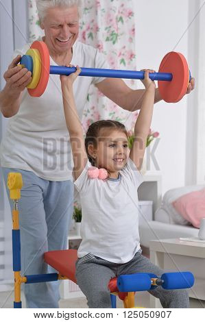 senior man and little granddaughter doing exercise at home