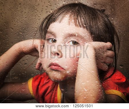 Sad kid in rainy weather at the window.