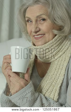 sick senior woman  with cup of tea at home