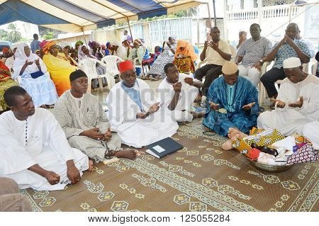 Abidjan, Ivory Coast - February 26, 2015: Religious leaders are doing the last prayer to bless the newlyweds. Sitting on mats placed on the floor, religious leaders, open and outstretched hands made their last prayer for the succeful mariage.