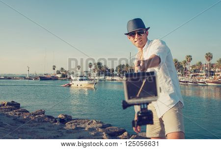 handsome man with action camera take a selfie photo in the tropical sea bay