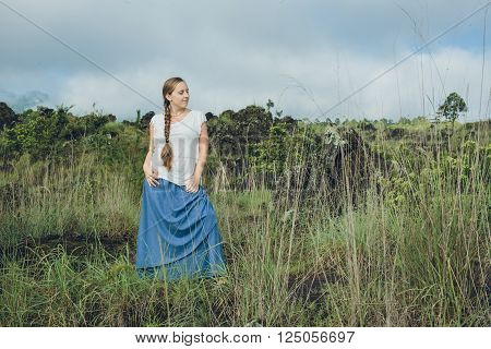 Young Woman looking on Batur volcano and Agung mountain view at morning from Kintamani Bali Indonesia