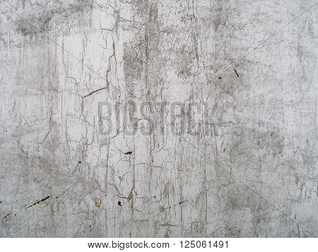Close-up of cracked paint on the wall. Old weathered painted wall surface. Grunge background with peeling paint