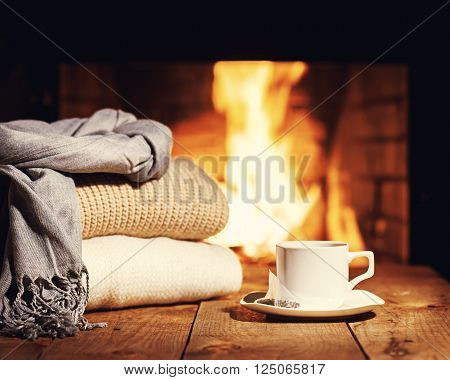 .white Cup Of Tea And Warm Woolen Things Near Fireplace.