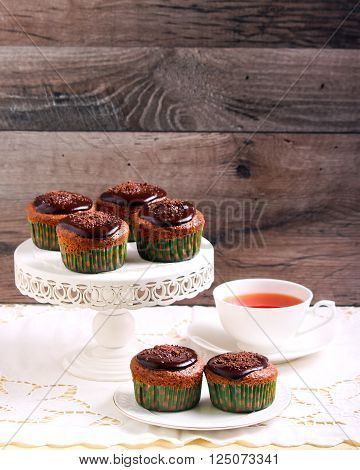 Lighter chocolate cupcakes and tea selective focus