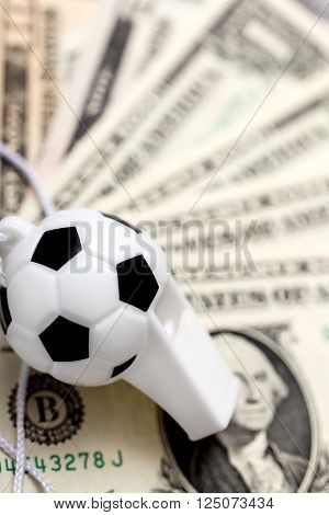 soccer whistle on dollar notes concept sport bets or corruption