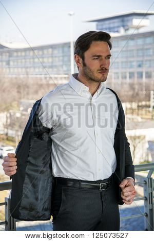 Head and Shoulders Portrait of Stylist Young Man Wearing Suit and Hat Looking to the Side Out Window While Standing on Moving Sidewalk in Building ** Note: Soft Focus at 100%, best at smaller sizes