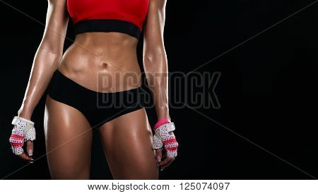 Part of the beautiful body of a young sporting girl on dark background. The concept of sport, healthy lifestyle, beauty, waist, flat stomach.