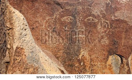 Face petroglyph carved into rock at Three Rivers Petroglyph Site in New Mexico