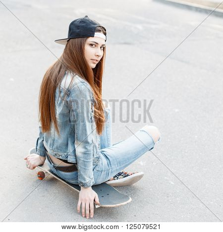 Young Stylish Girl In A Denim Jacket And Jeans Sitting On A Skateboard.